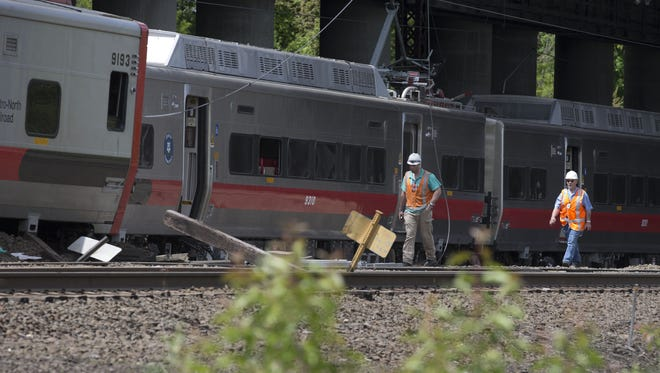 Connecticut state investigators examine the scene of a Metro-North Railroad train collision May 18, 2013, in Connecticut. Two New Haven Line commuter trains collided May 17, 2013, injuring as many as 70 people.