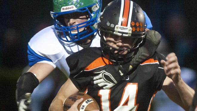 Colchester's Grant Cummings corralled Middlebury's Austin Robinson (14) in a 2014 high school football game.