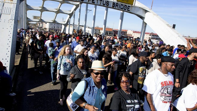 """Thousands of marchers cross the bridge in 2017 during the the 51st anniversary of the voting rights demonstration that came to be known as """"Bloody Sunday,"""" during the re-enactment of the march across the Edmund Pettus Bridge in Selma."""