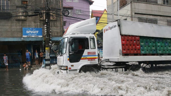 A delivery truck negotiates flooded roads as Typhoon Rammasun batters suburban Navotas, north of Manila,  Philippines on Wednesday, July 16, 2014. Typhoon Rammasun knocked out power in many areas but it spared the Philippine capital, Manila, and densely-populated northern provinces from being directly battered Wednesday when its fierce wind shifted slightly away, officials said.  (AP Photo/Aaron Favila)
