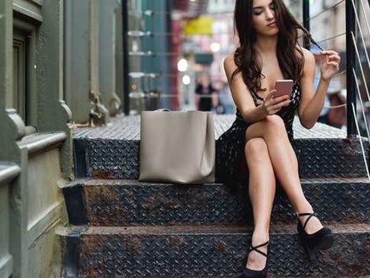 A pretty young woman sits on front stoop using her
