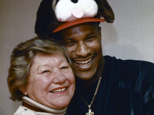 Reds President Marge Schott hugs center fielder Eric Davis, sporting a Schottzie hat, after he signed a record deal (with incentives) to play for the Reds.