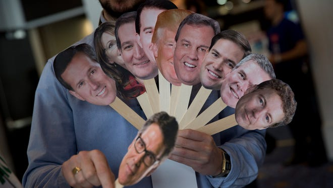 Adam Gabbatt of The Guardian newspaper holds images of potential Republican candidates, from left, Rick Santorum, Sarah Palin, Ted Cruz, Scott Walker, Donald Trump, Chris Christie, Marco Rubio, Jeb Bush, Rand Paul, and below, Rick Perry, during the Conservative Political Action Conference on Feb. 26, 2015.