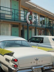 Vintage cars from the 1960s sit parked beneath the
