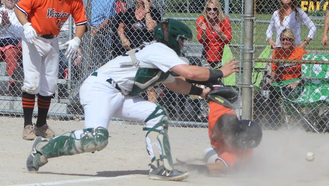 Brother Rice junior Jack Orlowski safely slides into home plate past Groves catcher George Cutler during a game-winning seventh inning rally to win the district championship Saturday afternoon.
