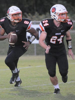 MTCS quarterback Joe Peck (8) rolls out while junior Andrew McConnell (24) looks to block during a recent game.