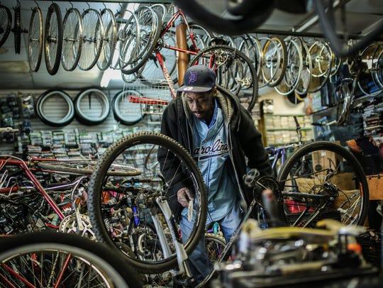 Travis Baddie, 43, of Detroit works on a bike inside