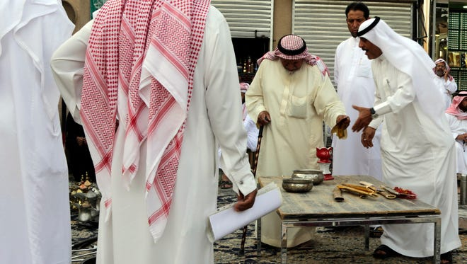 In this April 16, 2015 photo, Saudi men bargain to buy traditional Saudi swords and daggers at al-Aqeeliya open-air auction market in Riyadh, Saudi Arabia.