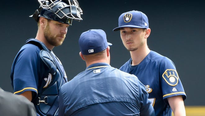 Brewers pitching coach Derek Johnson talks with pitcher Zach Davies (right) and catcher Jett Bandy  during a game.