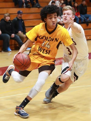 Golden West's Shemar Smith drives past Mt Whitney's Jed Whetstone during a WYL boys basketball game.