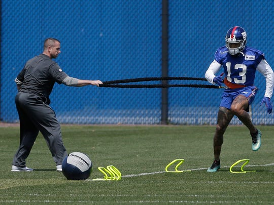 New York Giants' Odell Beckham Jr., right, works with a trainer during NFL football training camp in East Rutherford, N.J., Tuesday, April 24, 2018.