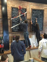 Employees put the finishing touches on the menu boards