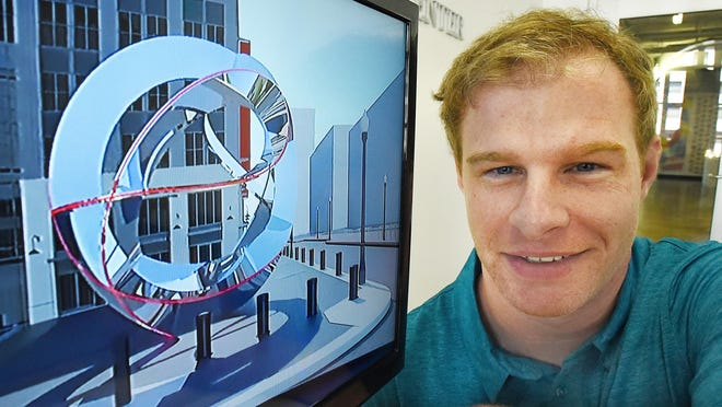 """College for Creative Studies student Jonathan Phillips views a video of his sculpture """"Movement of Champions"""" which will be installed in front of the new Little Caesars Arena when completed in Detroit, Michigan on May 15, 2017."""