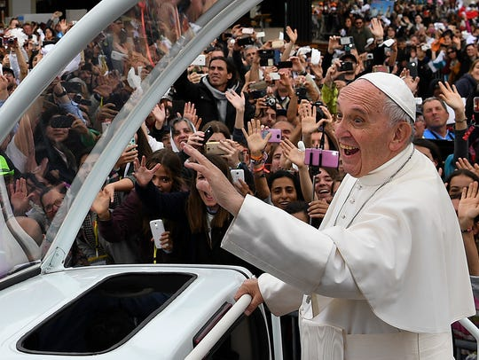 Pope Francis waves to faithful from the popemobile