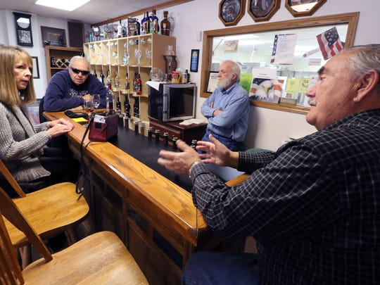 Peter Laundre (right) and Henry Gutmann talk with long-time friends and customers Cheryl and James Oliva of Pewaukee at the Two Brothers Winery tasting bar