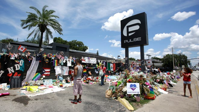 Visitors take photos and leave items at a makeshift memorial outside the Pulse nightclub on July 11, 2016, in Orlando, Fla.