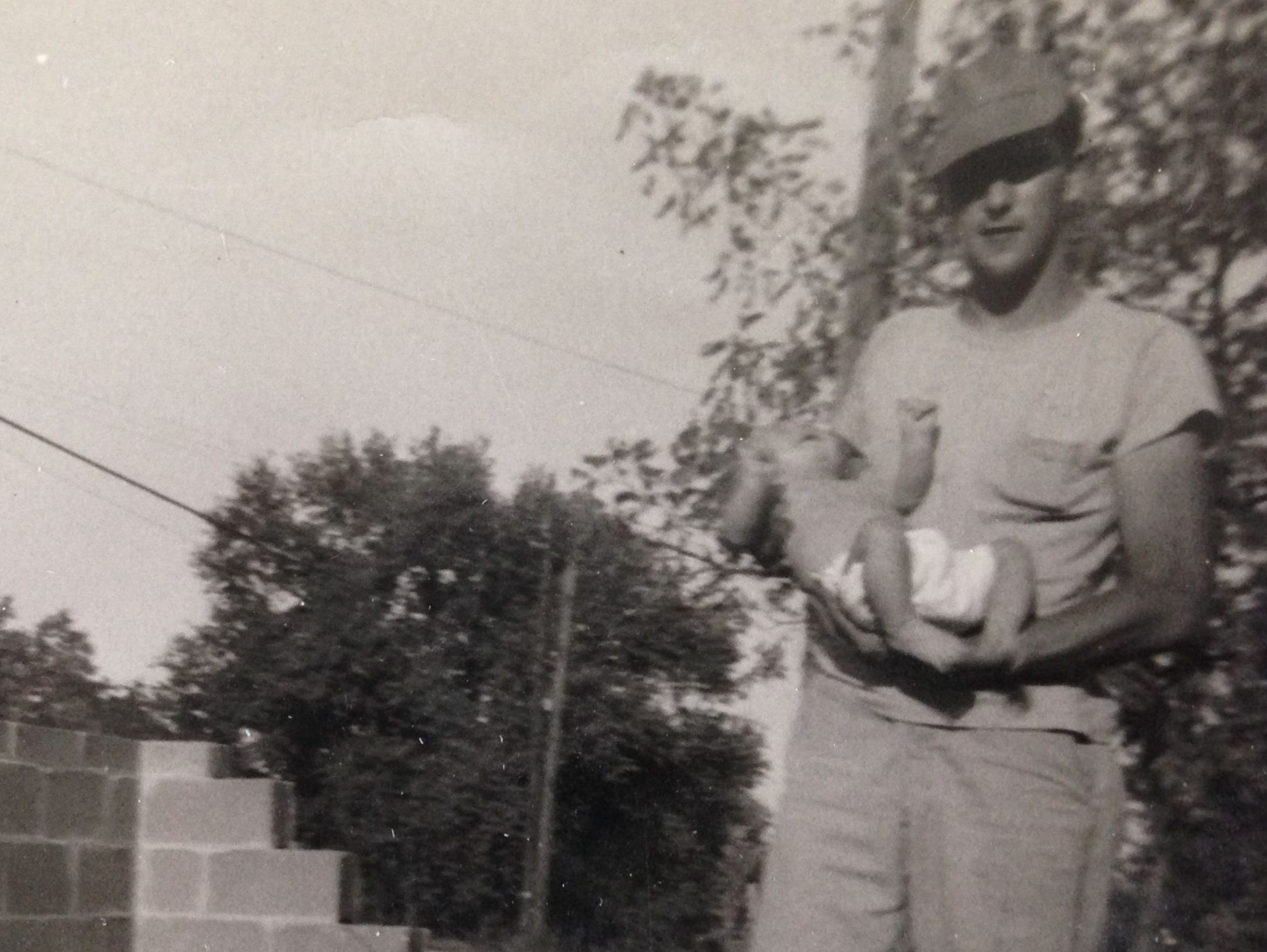 Eugene Flynt holds his baby son, Richard, at a home