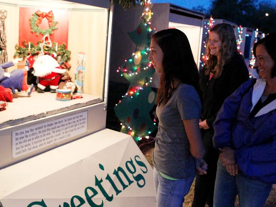 """Kirstin Bell (left), with her friend Brianna Furman and mother Leslie Bell, walk down the line of shadowboxes depicting the Christmas story """"Twas the Night Before Christmas"""" on display in the Santa Rita neighborhood in San Angelo in 2013."""