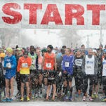 Snow continues to fall as runners wait to start the 22nd annual Thanksgiving Day Run on College Avenue in Old Town Thursday, November 26, 2015.
