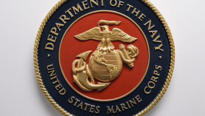 This photo shows the United States Marine Corps emblem hanging on a wall.