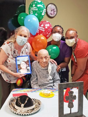 """Rufino """"Ralph"""" Lambertiz (center) celebrated his 106th birthday on Tuesday, August 25 with a small party thrown by the staff of Williston Healthcare & Rehabilitation. Pictured with him are Administrator Brenda Ridenour, Speech and Language Therapist Martina Price, and Activities Director Jasmine Wingard. Loved one Joanne Cagle joined via FaceTime."""