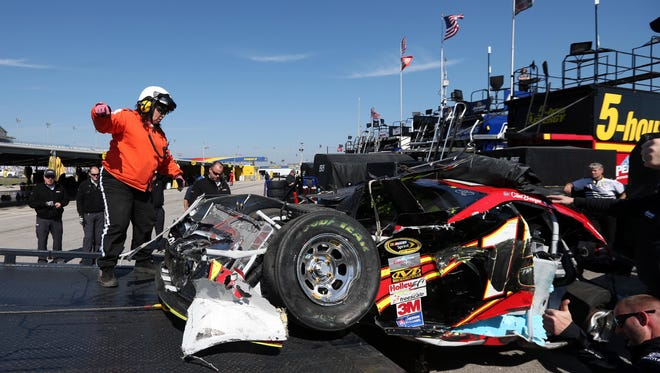 The wrecked car of Sprint Cup Series driver Clint Bowyer (15) is lowered at his hauler during qualifying for the Daytona 500 at Daytona International Speedway on Feb. 15.