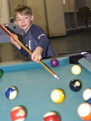 Leon Tabbert, 8, learns to play pool during the opening