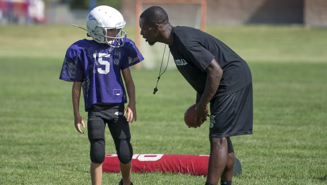 Former CSU cornerback Bernard Blake, right, instructs a youth football player in Fort Collins in this 2014 file photo. Blake has started a charity in his hometown of Bastrop, Texas, called Backed by Bam.