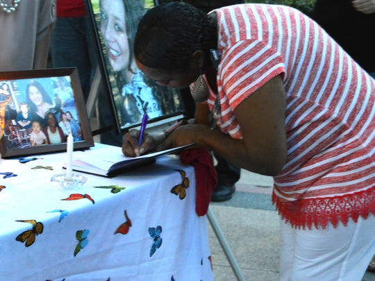 Edna Robinson signs her daughter's name in a memorial journal at a remembrance vigil for murder victims.