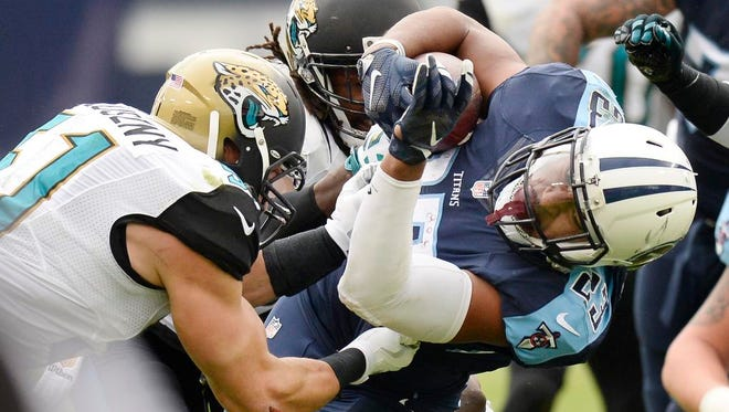 Tennessee Titans running back David Cobb (23) is hit by Jacksonville Jaguars defenders Paul Posluszny, left, and Davon House, center, in the first quarter at Nissan Stadium.