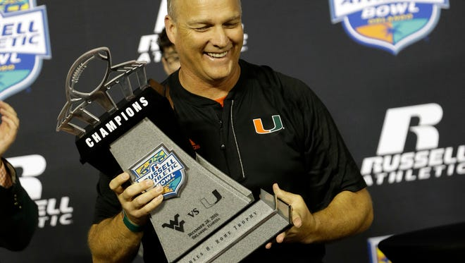 Miami head coach Mark Richt holds up the championship trophy after defeating West Virginia 31-14 in the Russell Athletic Bowl NCAA college football game, Wednesday, Dec. 28, 2016, in Orlando, Fla. (AP Photo/John Raoux)