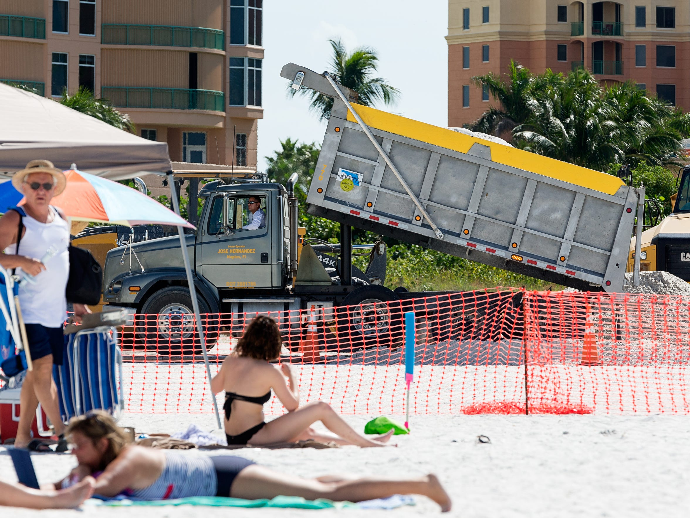 Dump trucks deliver sand from an inland mine to South