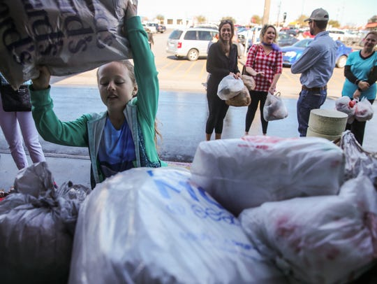 Ella Elkins, 8, collects plastic grocery bags during
