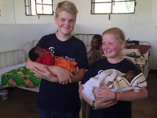 Gabe and Livvy Feinn pose with some newborns in the hospital they helped renovate with their baking and donations.