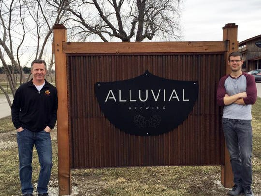 Marc Bailey, right, and his dad, Clint, pose in front of Alluvial Brewery in rural Ames.