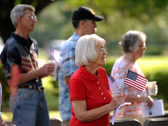 """Patsy Smith sings """"God Bless America"""" while hold a flag during the Memorial Day ceremony on Monday, May 29, 2017, at Elmwood Memorial Park. Smith's husband is a veteran and is buried at Elmwood."""