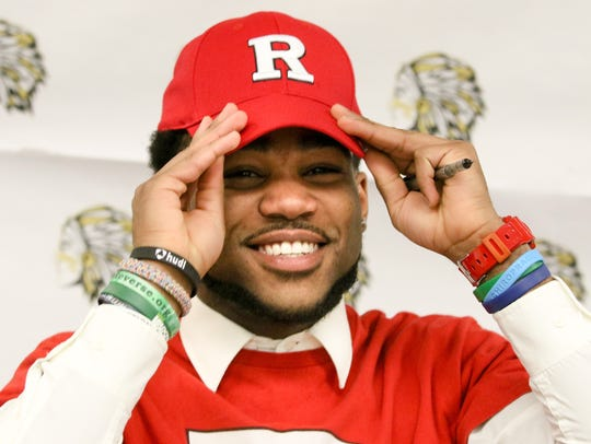 Piscataway football player Elijah Barnwell puts his Rutgers hat on after signing a National Letter of Intent to attend the state university last year.