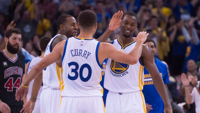 November 20, 2015; Oakland, CA, USA; Golden State Warriors guard Andre Iguodala (9), guard Stephen Curry (30), and forward Harrison Barnes (40) celebrate during the fourth quarter against the Chicago Bulls at Oracle Arena. The Warriors defeated the Bulls 106-94. Mandatory Credit: Kyle Terada-USA TODAY Sports