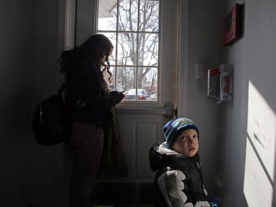 Ashlee Delgado checks her phone to see when the cab will arrive to take her to the grocery store while waiting with her son, Carmelo Monge, at her home in Spring Valley, N.Y., on Feb. 8, 2018. Delgado's registration had been suspended over unpaid tolls on the Gov. Mario M. Cuomo Bridge. To clear the suspension, she had to pay $1,548 - towing, storage, DMV fines, tickets, defensive driving class - and that didn't include the $3,500 in violations.