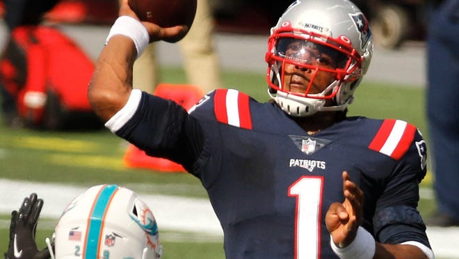 Patriots quarterback Cam Newton winds up to pass to a receiver in the season opener against Miami at Gillette Stadium. Newton has been working with the Patriots coaches to improve his throwing mechanics.