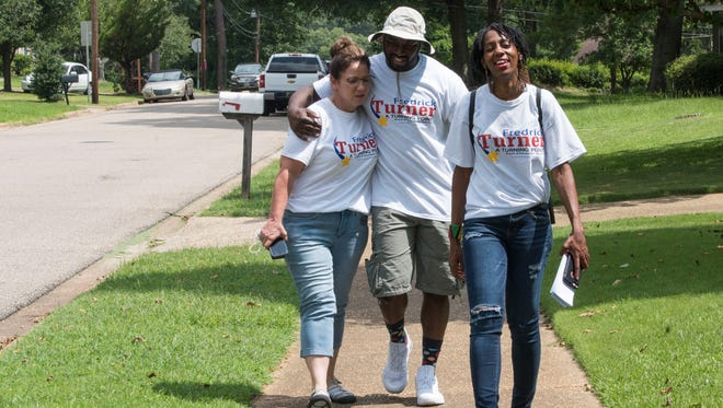 Fredrick Turner, Democratic candidate for Montgomery County Board of Education District 1, walks with volunteers Beverly Williford, left, and LaToya Robinson, right, Saturday, June 16, 2018, as he campaigns to win the runoff in the Pecan Grove neighborhood of Montgomery, Ala.