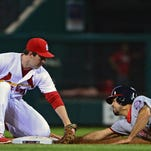 Cardinals second baseman Jedd Gyorko (3) applies the tag as Nationals third baseman Anthony Rendon (6) steals second base during the fourth inning at Busch Stadium.