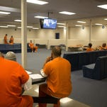 Inmates watch television in one of the newer intake areas at the Larimer County jail Oct. 9, 2014. Jail staffers working in the pod are credited with saving a man's life Tuesday morning.