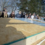 Asheville Area Habitat for Humanity volunteers hoist a wall for a house on Soulshine Court.