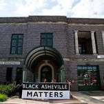 """Community members and organizers from Showing Up for Racial Justice hold up a Black Lives Matter sign outside the Asheville Police Department Thursday morning July 21, 2016. Organizers sat inside the station's lobby until the police meet their demands- accountability in the killing of Jerry """"Jai"""" Williams and an end to police violence towards people of color- or until they are arrested."""