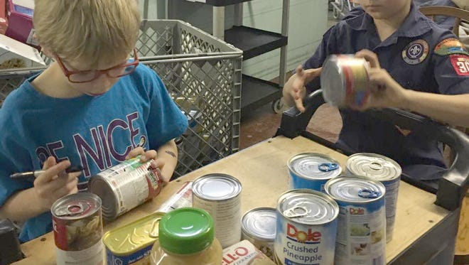Fairview Cub Scouts help process food items collected for GraceWorks West.