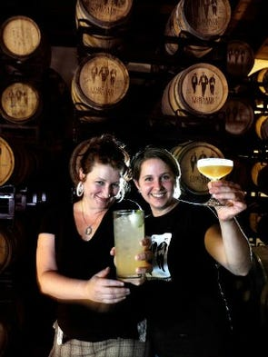 """Corsair Artisan Distillery """"Brew Fairy"""" Emily Kendall, left, and head distiller Andrea Clodfelter show off some of their cocktails in the aging room with oak barrels full of whiskey."""