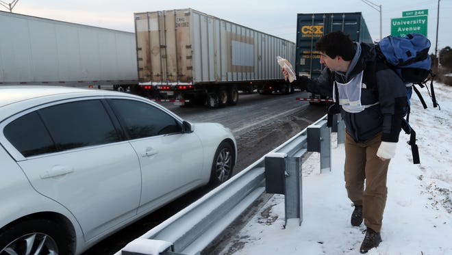 Matthew Miller walks along the Southbound Connector offering peanut butter and jelly sandwiches and hot drinks to motorists stuck in traffic in Atlanta. Miller, who lives in Grant Park, heard about the stranded motorists and decided to help.