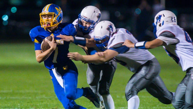 Milton's Jacob Laware, left, is pursued by Mt. Anthony defenders in Milton on Friday, September 22, 2017.