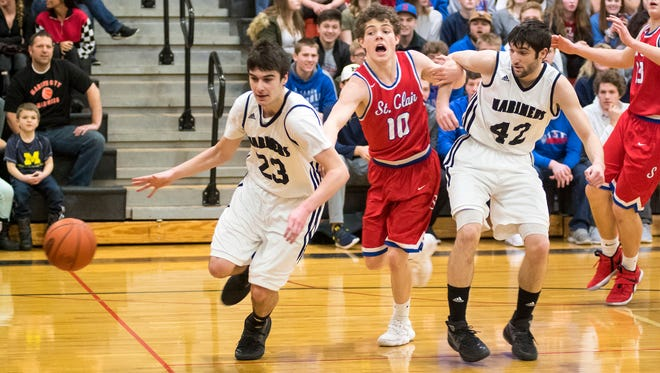 Marine City's Angelo Patsalis (23) and William Patsalis (42) and St. Clair High School's Mario Mattson chase a rebound during the MHSAA Class B District Semifinals at Marine City High School March 7.